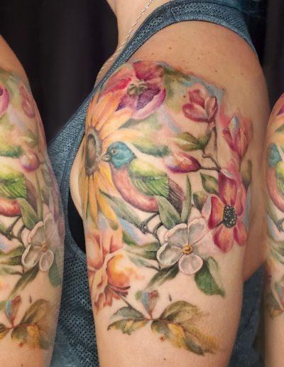 Watercolor floral half sleeve tattoo